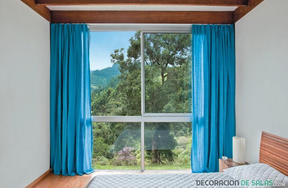 dormitorio con cortinas azules largas