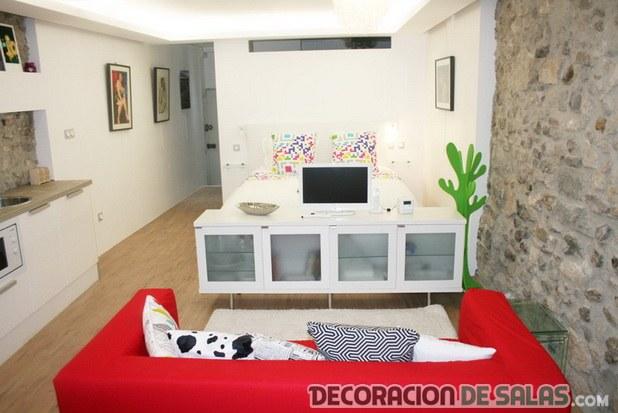 salón con mueble blanco y sofá rojo