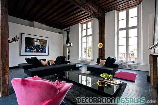 salón con sofás negros y rosa