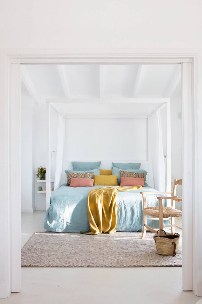 edredon azul y dormitorio blanco