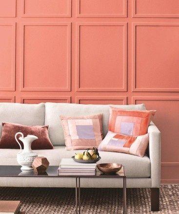 Paredes coral y sofá blanco